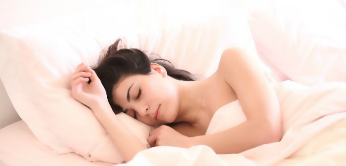 Woman sleeping in bed with fresh white bedding - How to get a Good Nights' Sleep if you Suffer from Back Pain