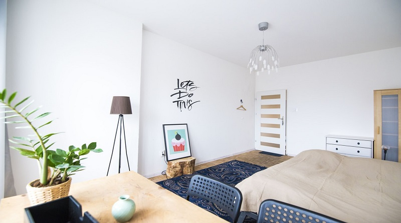 Studio Apartment with a Plant, Floor Lamp, Desk, Bed and Picture of a Big Pink Cupcake