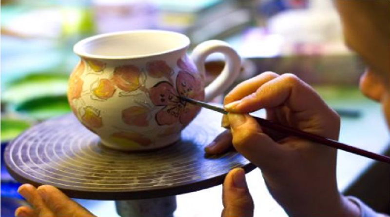 Artist painting an abstract floral design onto a cup.