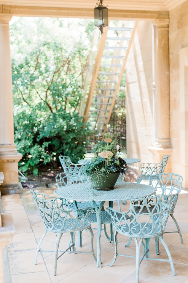Top Tips for Designing an Outdoor Room  Patio with stone paver flooring and wrought iron table and chairs.