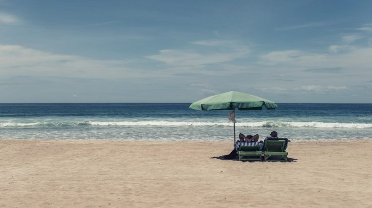 BEST TIPS TO FUND YOUR LAST MINUTE HOLIDAY Couple Relaxing in chairs under an umbrella on a quiet beach.