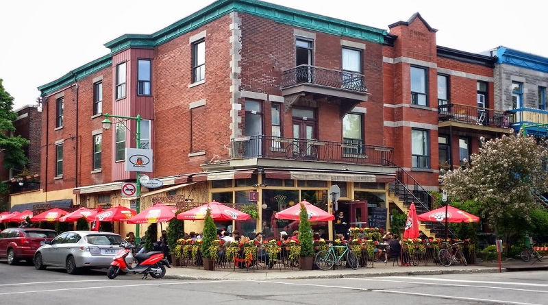 3 story red brick building with lovely landscaping outside, with tables and chairs and red shade umbrellas.