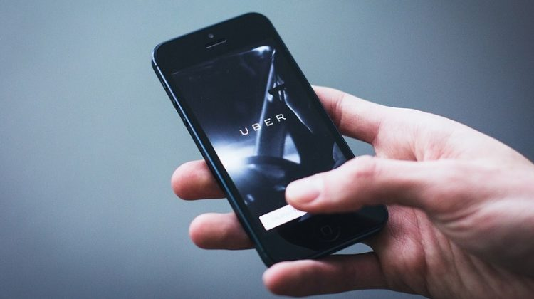 Hand holding a smart phone with Uber app open