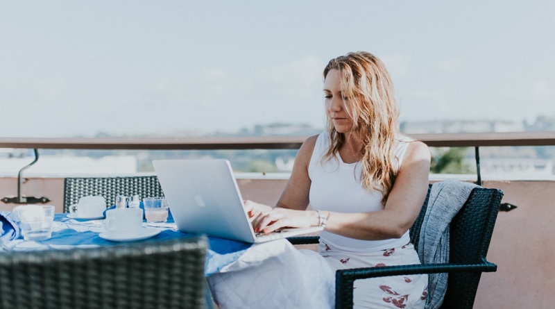 Woman working on computer at table on the beach - Essentials You'll Need To Work And Travel Successfully
