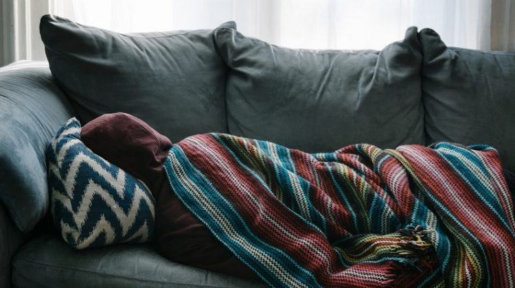 Person in Hoodie Sleeping on Sofa - Signs that It's Time for a Viatical Settlement