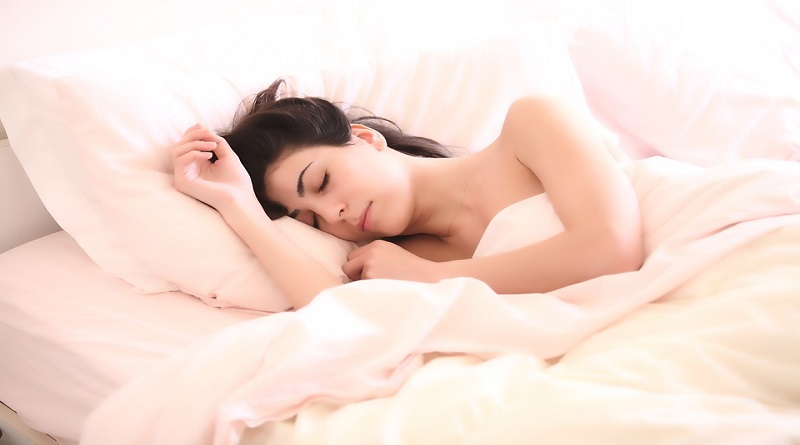 Woman with brown hair sleeping on a bed with white sheets.