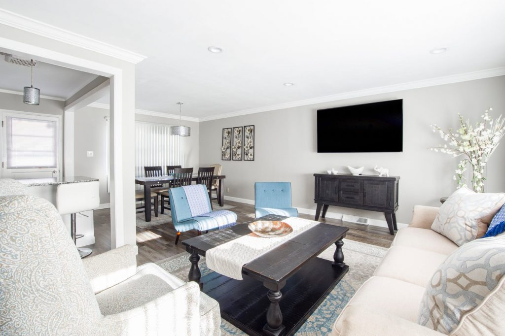 Bright living/dining room with white walls and a mix of white and turquoise upholstery, and dark wood - Making A Bright And Inviting Home For The Whole Family