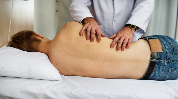 Doctor adjusting man on table -Aching Back? 5 Ways to Find a Chiropractor to Get You Back in Shape