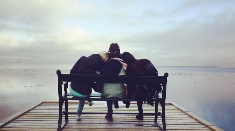 Friends sitting on a bench at the end of a dock on a lovely lake - 5 Ways To Support Alcohol Addiction Recovery