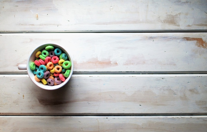 A bowl of sugary kids cereal on a white wooden table - Trying to Stay Sane While Facing Major Life Changes