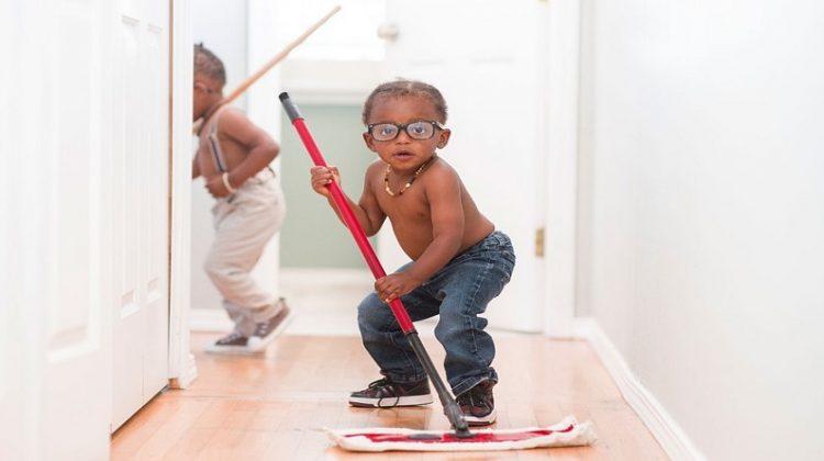 Adorable little boy helping to mop wood floor -