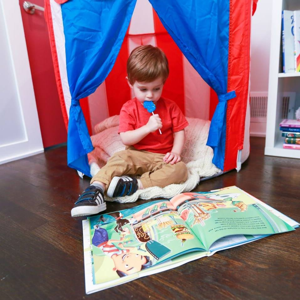 Little Boy Reading a Book and Enjoying a Lollipop - Put a Smile on Your Child's Face with The Lollipop Book Club