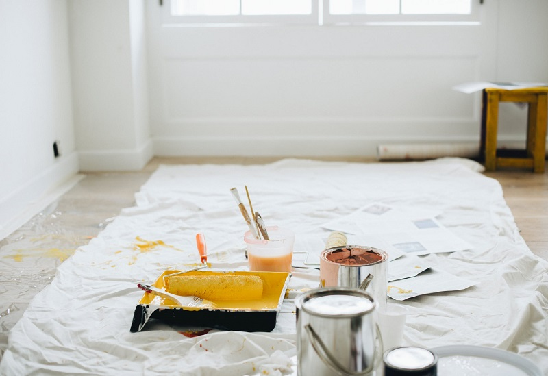 Paint and painting supplies laid out on a tarp in the middle of a room - Refreshingly Simple Budgeting Tips for Your Next Big Reno