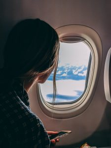 Woman looking out of airplane window - Last-Minute Getaway Ideas