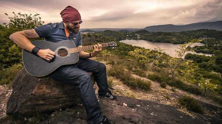 Guy playing a guitar in nature at sunset -3 Tips for Making Your Hobbies and Pastimes More Meaningful