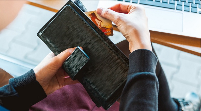 Woman taking a credit card out of a black wallet = Practical Ways To Save Money On Your Household Bills