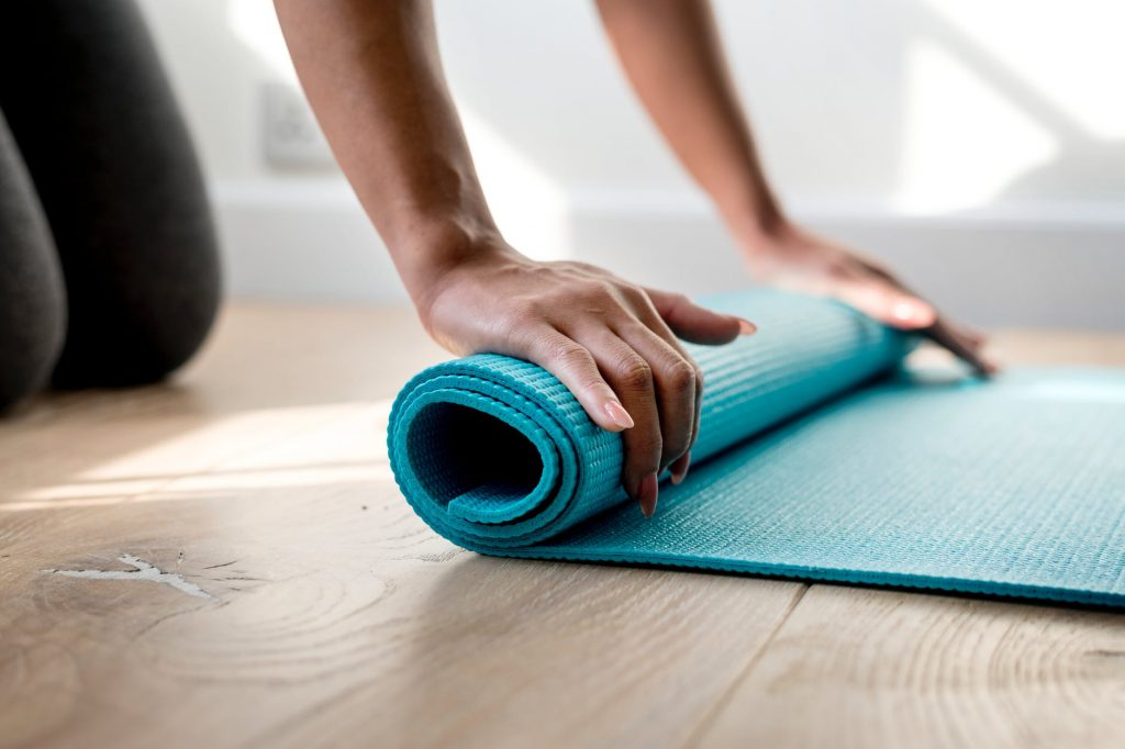 Woman rolling out Yoga Mat - 6 Family-Friendly Fitness Tools Every Home Should Have