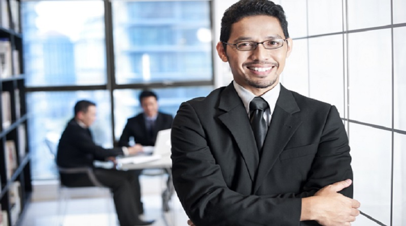 Smiling man in an office, wearing a suit - Solicitor