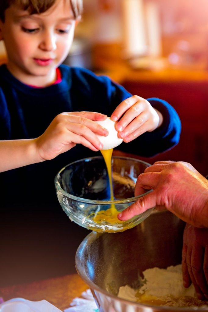 Little boy cracking an egg into a bowl - Giving a Child More Responsibility at Home