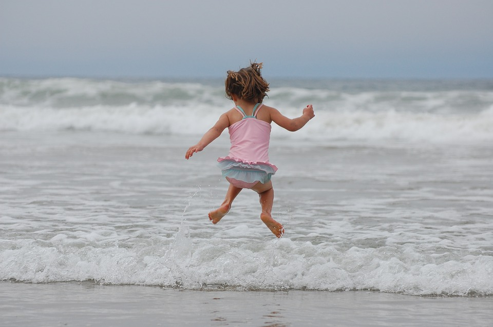 Little girl in bathing suit jumping by the ocean - Beach Vacations