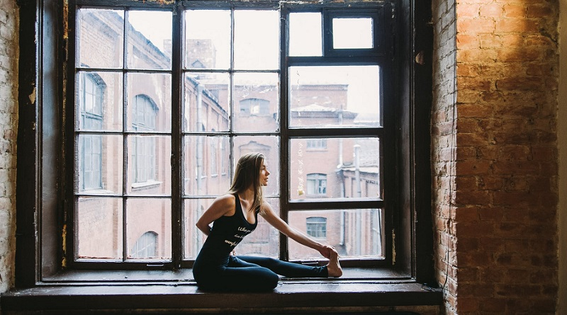 Woman Doing Yoga in Window Seat - At Home