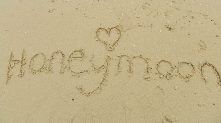 The Word Honeymoon written in the sand.