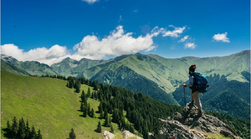 Man Standing on Rock Looking Over Valley - Top 5 Must Have Travel Gadgets