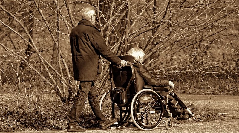 Man Pushing Woman in a Wheelchair - Keeping Balance: 5 Tips for Avoiding Caregiver Fatigue