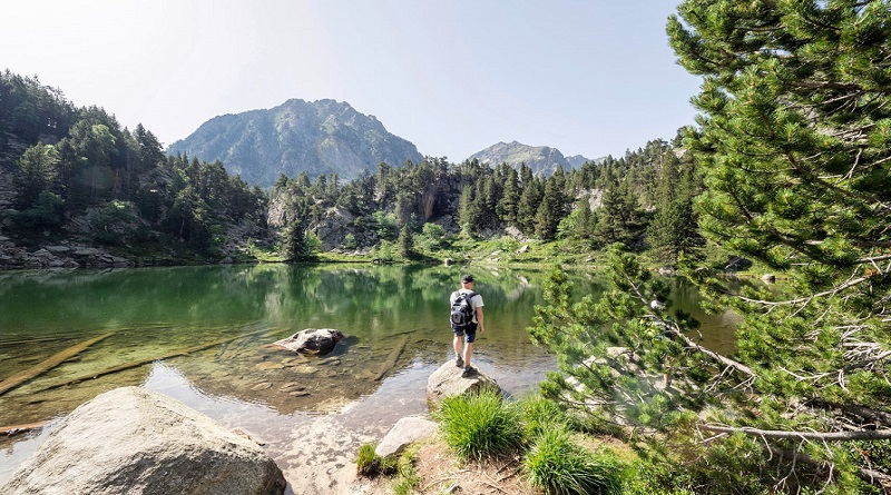 Backpacker standing in forest by lake - 5 Gift Ideas for the Minimalist Adventurer in Your Life