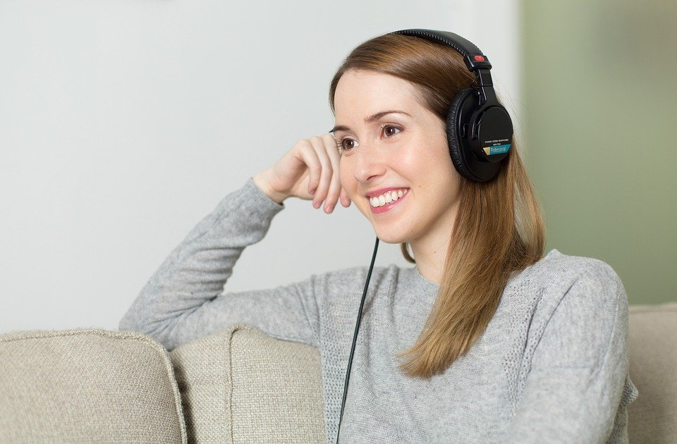 Smiling Woman Wearing Headphones - Your Smile Affects What People Think Of You