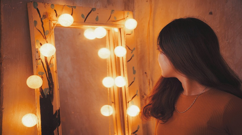Woman with Brunette Hair and Wearing a brown top, looking into a lighted mirror -How To Like Yourself