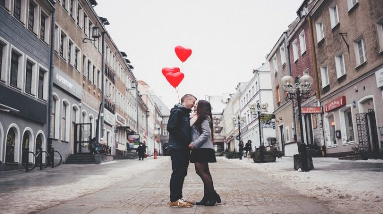Loving couple standing in old city street with red heart balloons - fun date night ideas