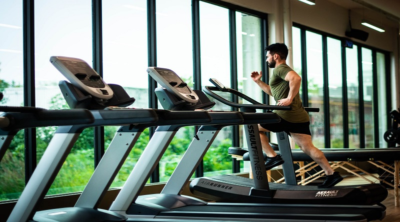 Man running on treadmill in gym - Cultivate Better Habits