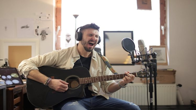 Man singing and playing guitar in home recording studio -