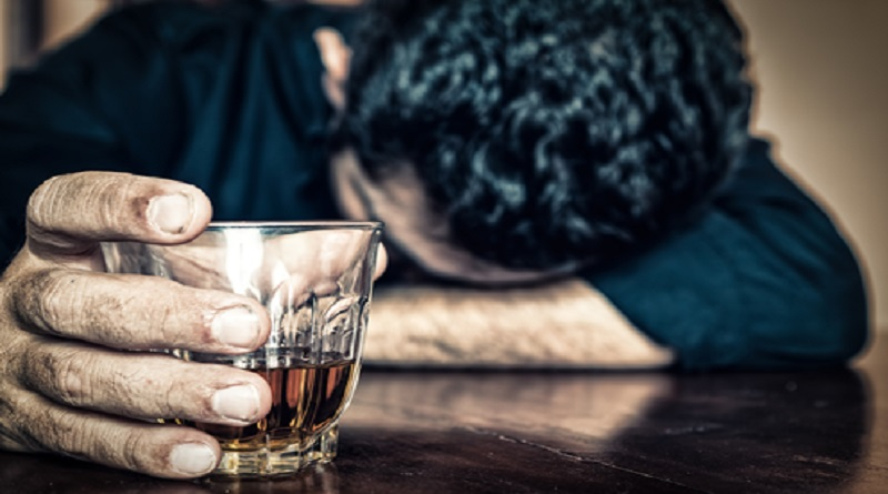 Man with head down on table holding glass of liquor - Alcohol Addiction