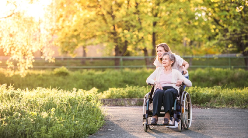 Young woman pushing an older women in a wheelchair down a path in a park -Medicare if You Have ALS or ESRD