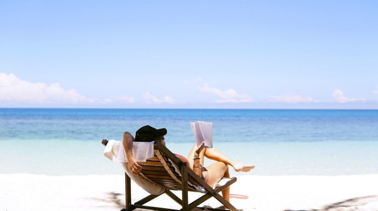 Woman reading in lounge chair on beach - Signs You Need a Holiday