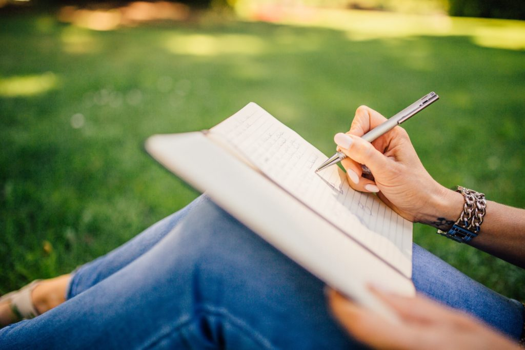 Woman sitting on grass and writing in notebook - Cultivate Better Habits