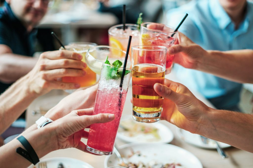 Group of people doing cheers with cocktail glasses - Cultivate Better Habits