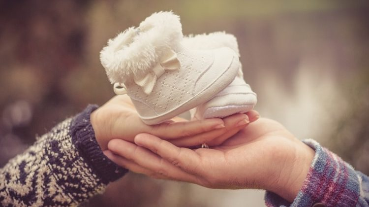 Man and Woman's Hands Holding Baby Booties - Help A New Mom