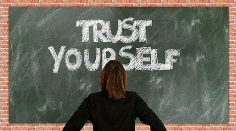 Woman standing in front of chalkboard on brink wall - Boost Your Self Confidence
