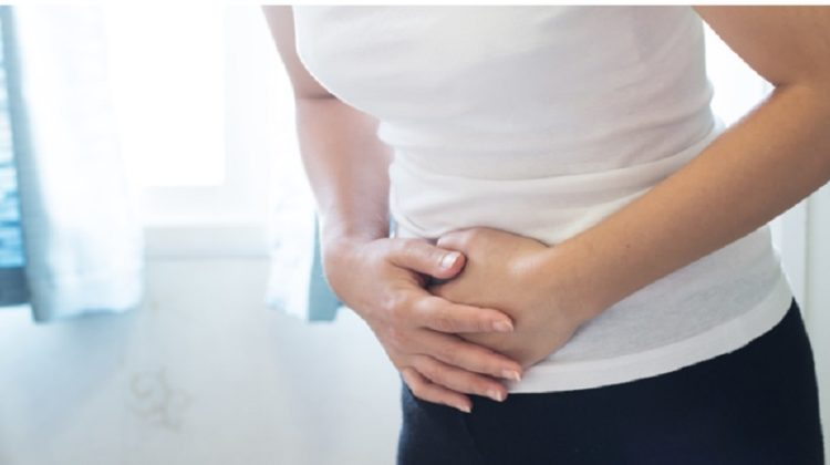 Woman in White Shirt and Plant Pants Holding Her Stomach - Yeast Infection Relief