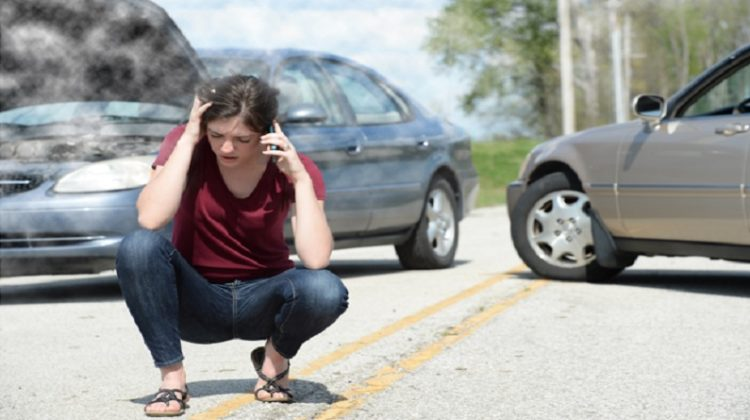 Woman talking on phone in front of wrecked cars. - Accident Doctor