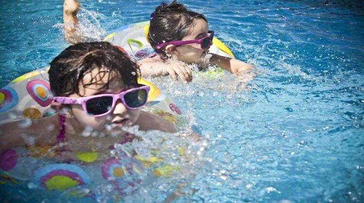 2 little girls wearing pink sunglasses in a pool - De-Winterize your Yard