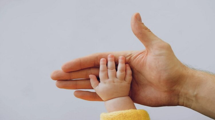 Baby hand in adult male hand - Cost to Raise a Disabled Child