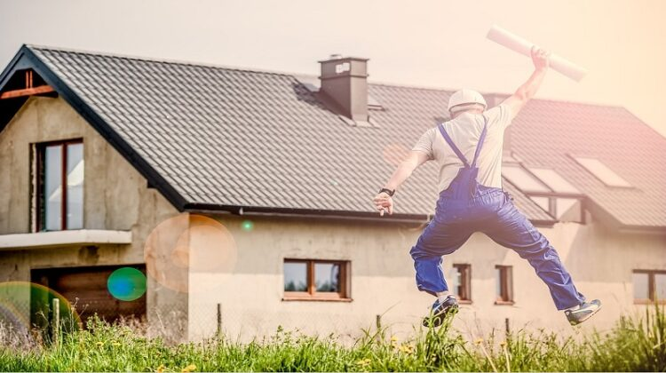 Man in overalls holding building plans, jumping in air in front of house - Your Dream Home