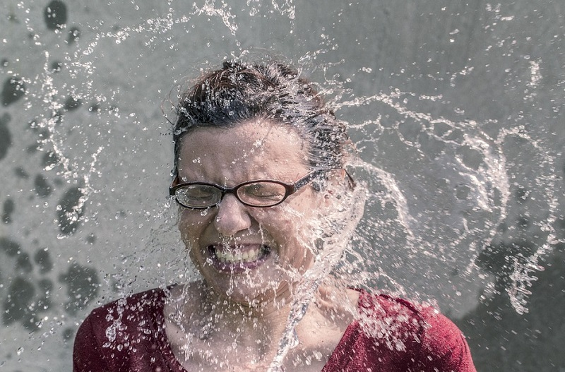 Woman in Red Top Wearing Glasses Getting Dumped with Water - Protect Your Home From Water Damage