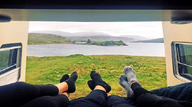 Three sets of legs in a campervan looking out over a large lake - campervan
