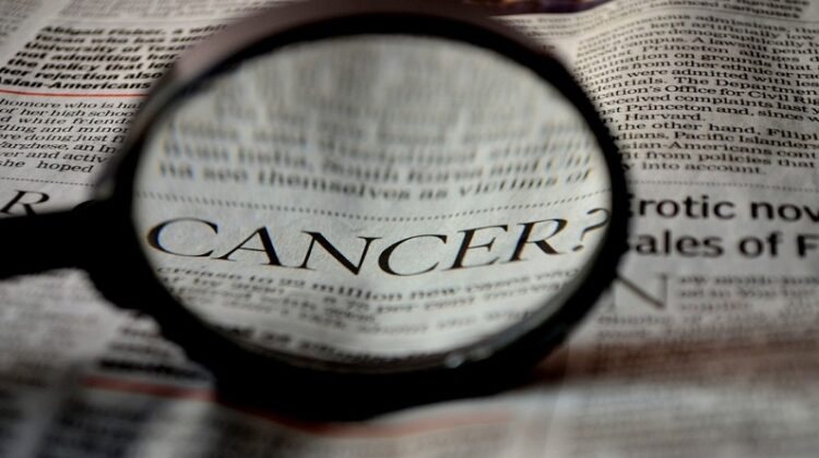Magnifying Glass over the word Cancer in a Newspaper - Understanding Various Types of Cancer