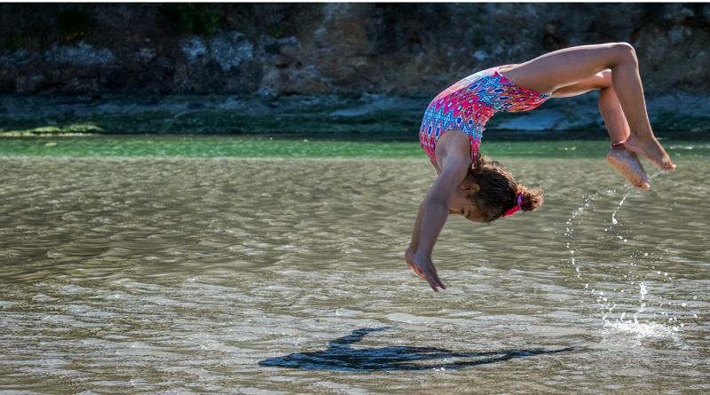 Little Girl doing flips in the water -